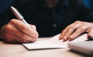 руки, держащие ручку. фото