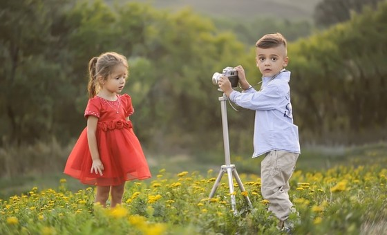 мальчик фотографирует девочку. фото