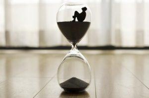 песочные часы с силуэтом человека. иллюстрация