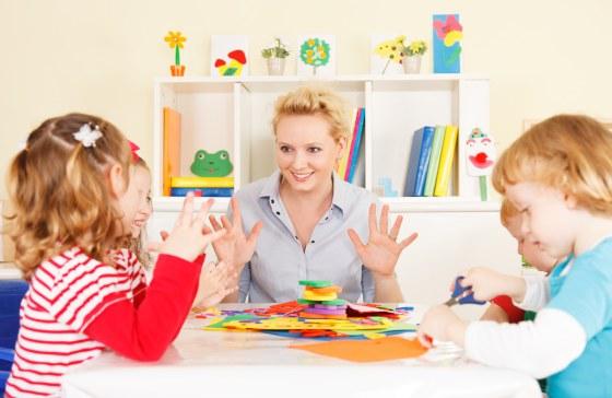 женщина играет за столом с детьми. фото