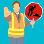 силуэт рабочего с дорожным знаком в руке. иллюстрация