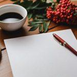 лист бумаги, авторучка и чашка с кофе. фото