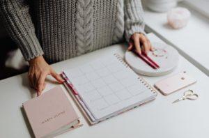 открытый ежедневник на столе, альбом для фото, смартфон и ножницы. фото