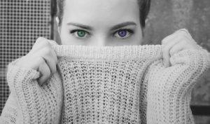 Женское лицо, наполовину закрытое воротником свитера. фото