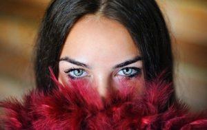 Женское лицо, наполовину скрытое ворохом перьев. фото