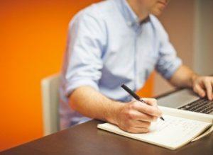 Рука пишет на бумаге. фото