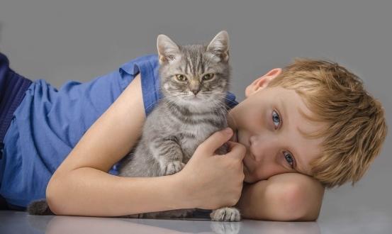Мальчик обнимает котенка. фото