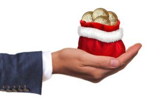 Рука с рождественским мешком и монетами. иллюстрация