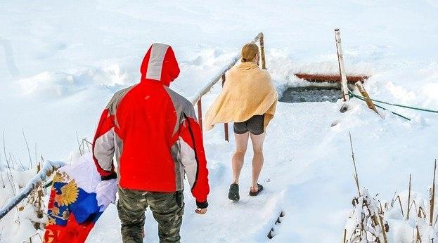 Мужчина и женщина подходят к проруби. фото
