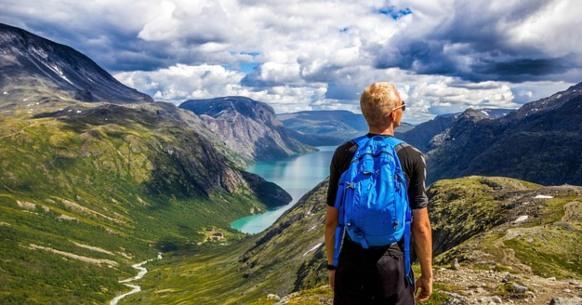 Парень смотрит на горный пейзаж. фото
